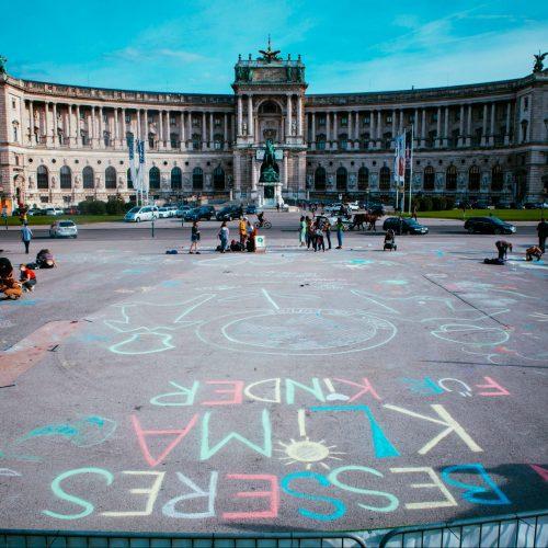 Foto vom Heldenplatz auf die Hofburg in Wien. Am Boden sind Botschaften zum Klimaschutz mit bunter Kreide aufgemalt.