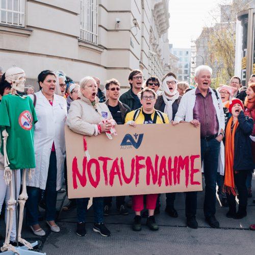Menschen in Arztkitteln und als Verletzte verkleidet stehen vor dem Sozialministerium. Sie halten ein Schild auf dem Steht: AUVA-Notaufnahme.