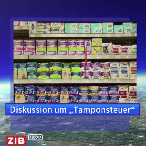 """Ein Ausschnitt aus dem ZiB-Fernsehstudio. Man sieht einen Beitrag eingeblendet: Ein Foto von einem Regal mit Monatshygieneprodukten. Darunter steht """"Diskussion um Tamponsteuer"""""""