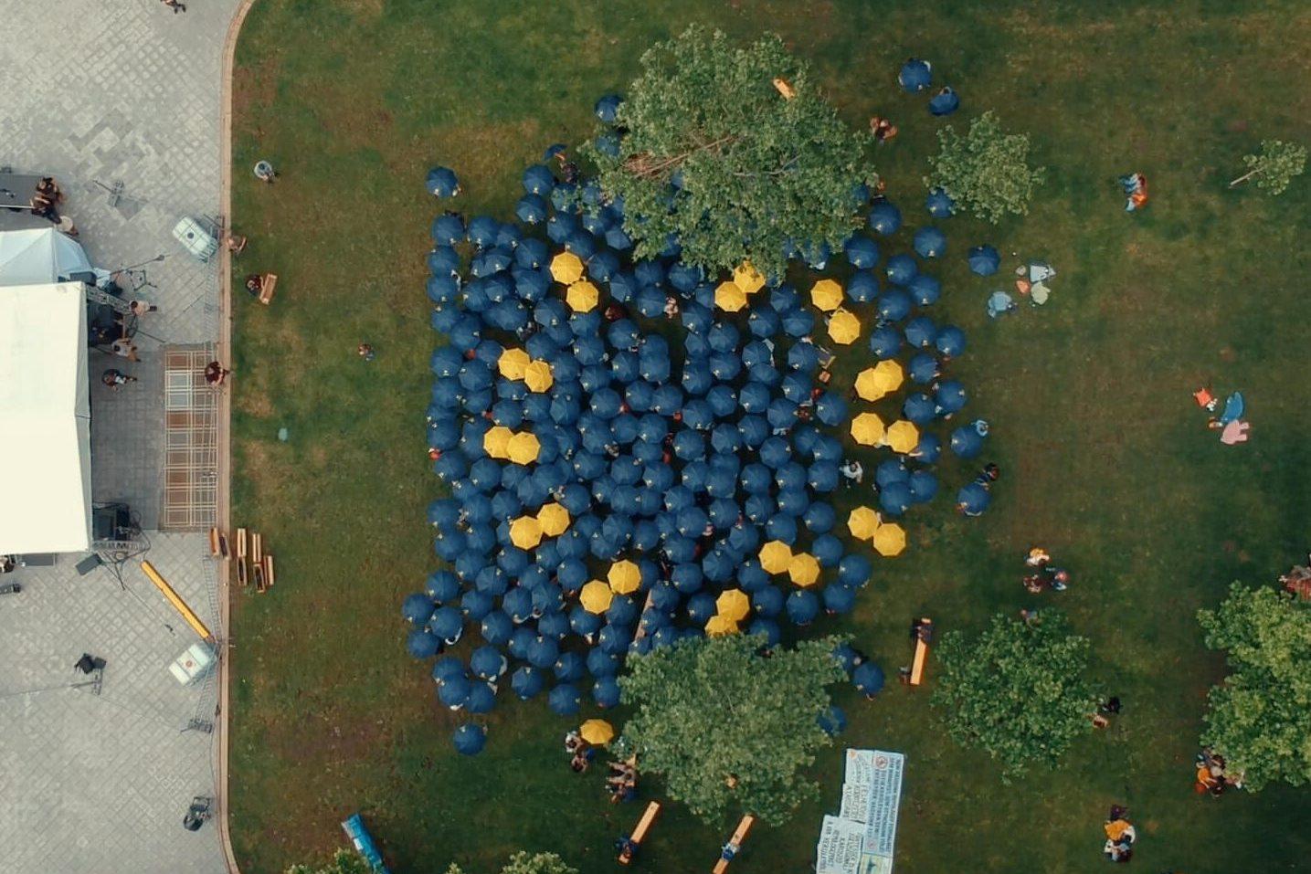 Luftaufnahme eines Flashmobs in Budapest - ca. 200 Menschen halten blaue und gelbe Regenschirme in die Luft und bilden damit die Flagge der EU.