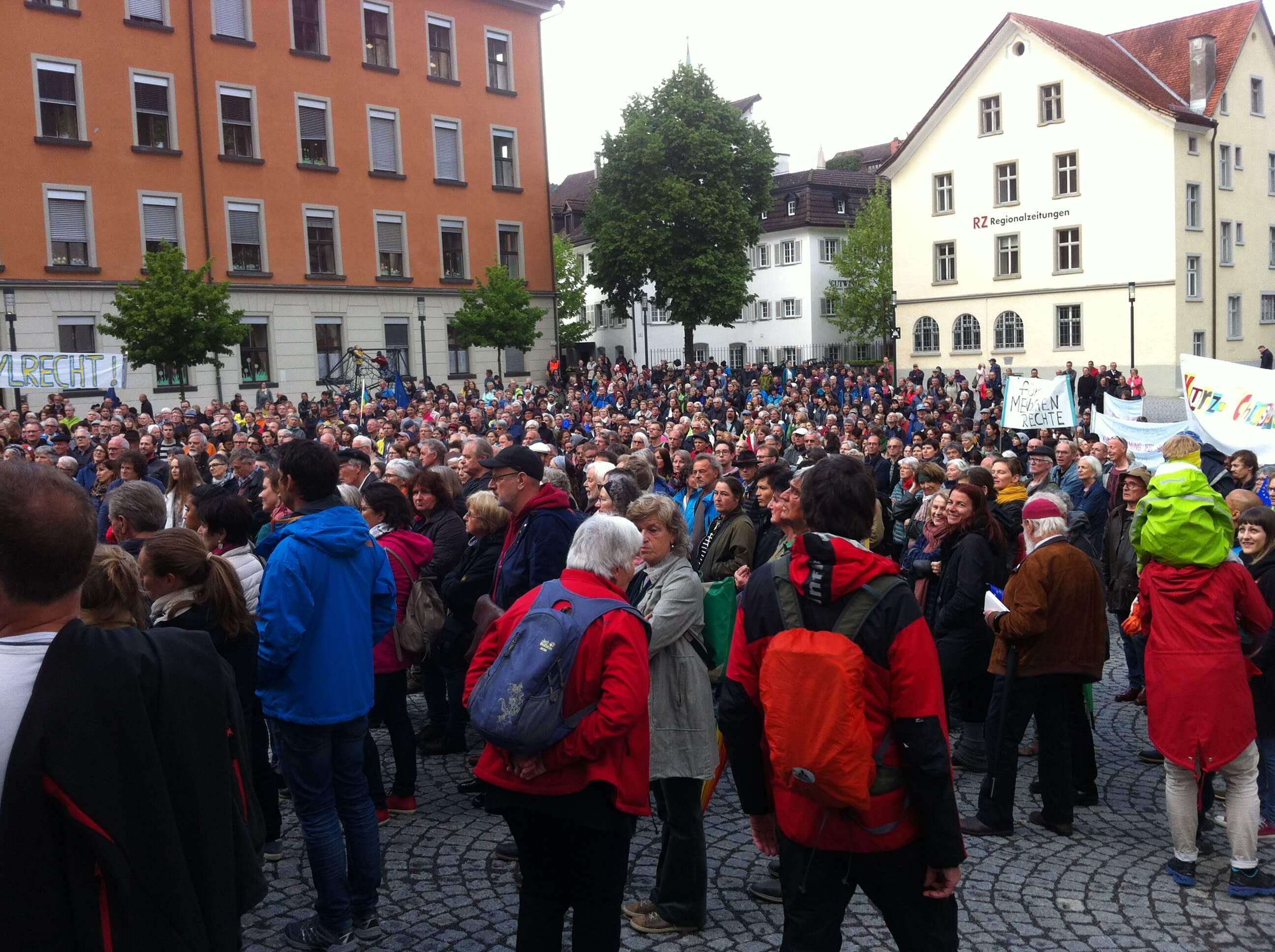 Ca. 900 Menschen stehen am Montfortplatz in Feldkirch. sie schauen Richtung Montforthaus. Manche halten Schilder und Banner in die Höhe.
