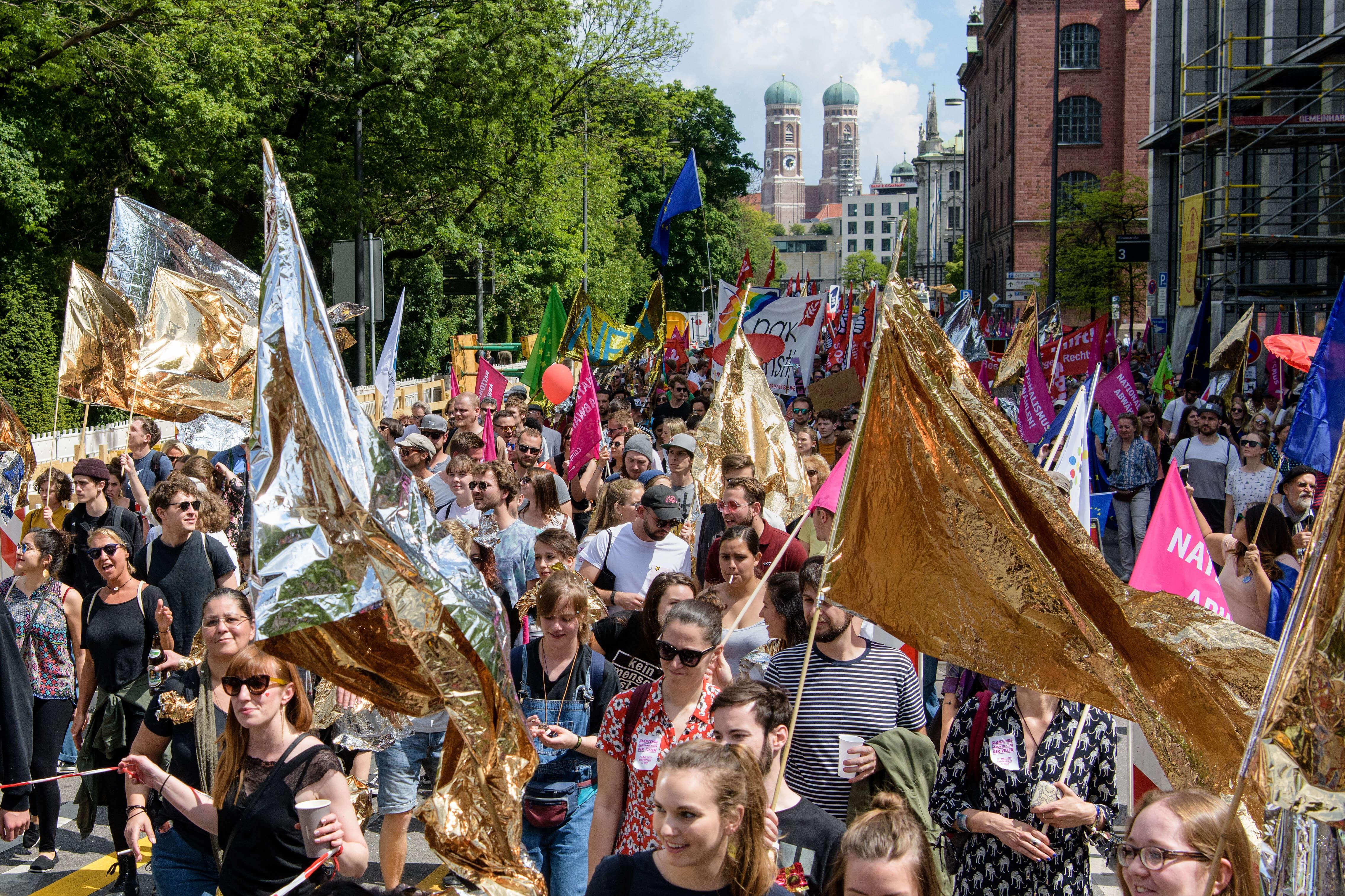 Demo-Teilnehmer_innen ziehen durch die Straßen in München. Im Hintergrund ist die Frauenkirche zu sehen. Im Vordergrund schwingen junge Menschen goldene Flaggen aus Rettungsdecken.
