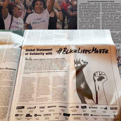 Auf dem Bild sieht man ein Inserat in der New York Times. Es zeigt die gemeinsame Solidaritätserklärung von #aufstehn und anderen Organisationen mit der Black Lives Matter Bewegung in den USA. Neben dem Text befindet sich eine Grafik mit zwei kämpferisch ausgestreckten Armen, einer mit schwarzer, einer mit weißer Hautfarbe.