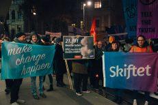 Demonstrierende und #aufstehn-Mitarbeiter_innen halten Fahnen und Schilder von den Partnerorganisationen Campax (mit dem Schriftzug: make change happen) und Skiftet in die Höhe