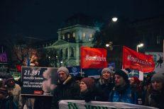 2 #aufstehn-Fahnen und ein Schild mit der Forderung an die OPEC werden von Demonstrierenden gehalten - im Hintergrund das Hauptgebäude der Universität Wien