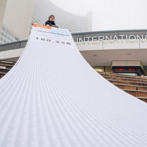 Maria Mayrhofer steht mit einem 18m langen schriftstück mit über 185.000 Unterschriften vor dem UN-Gebäude in Wien.
