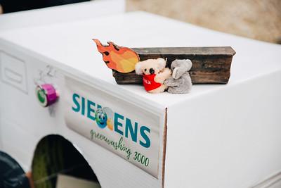 """Close-Up von 2 Koala-Stofffiguren auf der Kartonwaschmaschine. Sie umklammern sich, hinter ihnen ein """"brennendes Holzstück"""" aus Papier. Auf der Waschmaschine steht """"Sie Ens greenwashing 3000"""""""