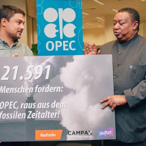 Raoul von #aufstehn und OPEC-Generalsekretär Mohammad Barkindo halten ein Schild, auf dem steht: 21.591 Menschen fordern: OPEC, raus aus dem fossilen Zeitalter!