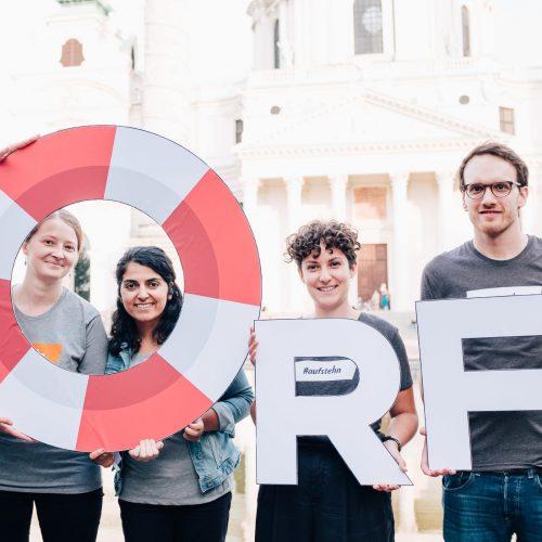 Vier junge Personen halten übergroße Buchstaben: O, R und F. Das O ist in Form eines Rettungsringes in rot und weiß.