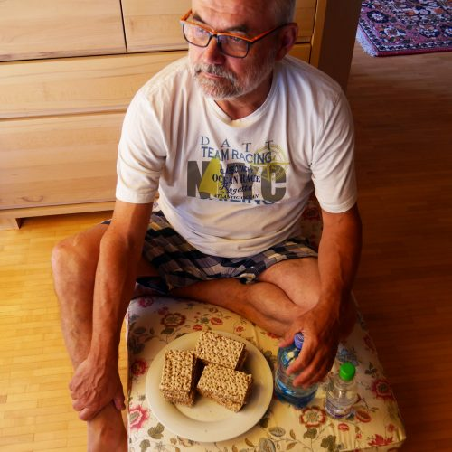 Ein Mann mit grauem Bart und weißem Shirt sitzt in seinem Wohnzimmer auf einem Polster am Boden. Vor ihm ein Teller mit drei scheiben Brot und eine Wasserflasche.