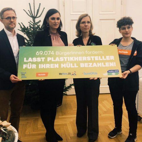 """Vertreter_innen unterschiedlicher Organisationen überreichen Umweltministerin Elisabeth Köstinger ein Schild auf dem steht: """"Lasst Plastikhersteller für ihren Müll bezahlen!"""""""