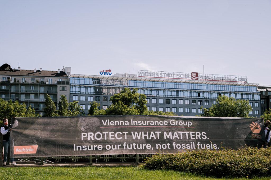 """Bildbeschreibung: Auf dem Bild ist im Vordergrund ein 10-Meter langes Banner zu sehen, auf schwarzen Hintergrund steht: """"Vienna Insurance Group: PROTECT WHAT MATTERS. Insure our future, not fossil fuels."""" Im Hintergrund ist ein modernes mehrstöckiges Gebäude zu sehen, auf dem das Logo der Wiener Städtischen Versicherung AG Vienna Insurance Group zu erkennen ist."""