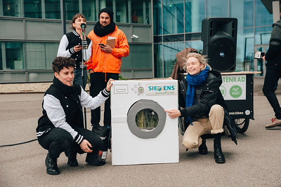 """#aufstehn-Mitarbeiter_innen präsentieren die """"Greenwashing-Maschine"""", eine weiße Waschmaschine aus Karton"""